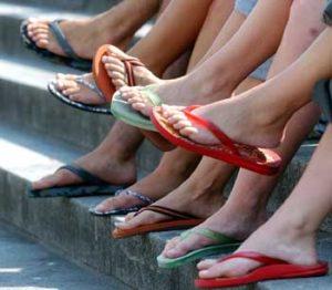 In ihren Flip-Flop-Sandalen genießen junge Leute am Dienstag (05.08.2003) an der Hamburger Außenalster den Sonnenschein. Flip-Flops sind die Trendsandalen des Sommers. Sie werden in den Hamburger Schuhläden ab fünf bis 200 Euro angeboten. Foto: Kay Nietfeld dpa/lno