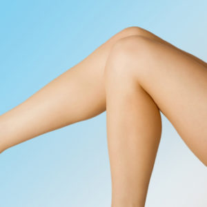 Female legs on blue gradient background.